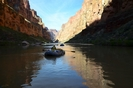 Raft floating down a glassy stretch of the Colorado River in Grand Canyon