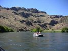 A gray raft on a smooth section of the Deschutes River with basalt cliffs in the background