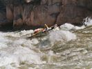 A white whitewater raft running down a steep rapid in the Grand Canyon