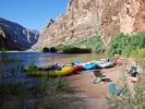 Bright yellow, red, and blue rafts on shore in the morning light with the Grand Canyon backdrop