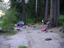 A sandy campsite at the edge of a dark forest of large trees