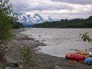 Red and blue rafts pulled up on gravel bar, with glaciers and mountains in the distance. Gray, overcast day.