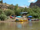 A colorful group of red, blue, and yellow whitewater rafts tied up at a campsite with blue umbrellas