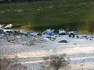 Looking down at four rafts and some women sitting on the beach at Johnson Creek Camp on the Main Salmon River