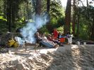 A rafting group sitting in the morning sun beside a campfire at Fawn Creek Camp on the Main Salmon River
