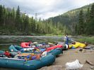 Green, yellow, and red rafts lined up in a row at Jim Moore Camp, Main Salmon River