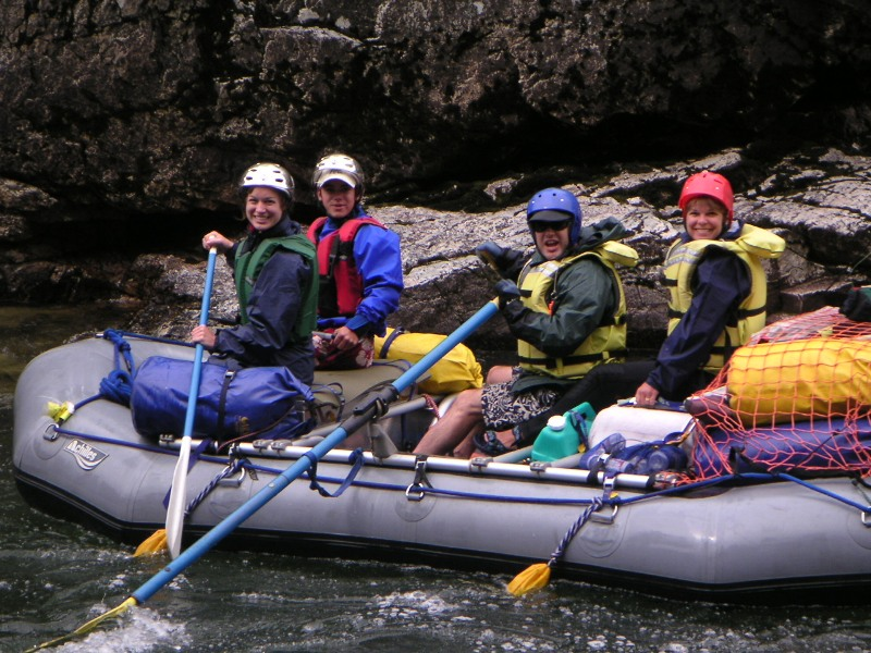 ca9eb4177f54 A whitewater raft with all occupants dressed in rain gear on the Middle  Fork of the