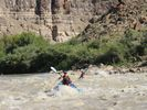Two girls rowing inflatable kayaks through a small rapid in Desolation Canyon